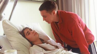 Szenenbild: ein junger Mann beugt sich über eine junge Frau, die in einem Krankenhausbett liegt.