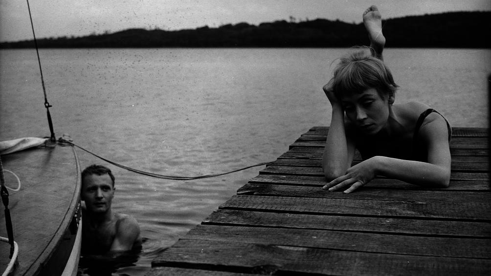 Karla liegt auf einem Bootssteg. Ihr Freund Jasper nähert sich vom Wasser.