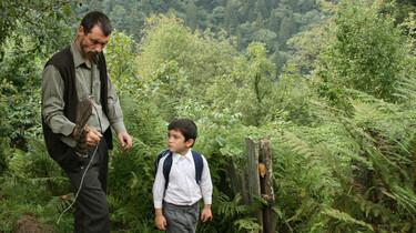 Szenenbild: Mann und kleiner Junge in grüner Umgebung, der Mann hat einen Raubvogel auf der Hand sitzen