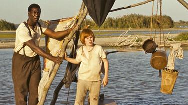 Szenenbild. Huck und Jim auf einem Floß in der Abendsonne