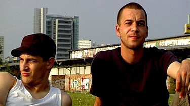 Szenenbild: Zwei junge Männer sitzen auf einer Wiese vor einer Bahnschiene