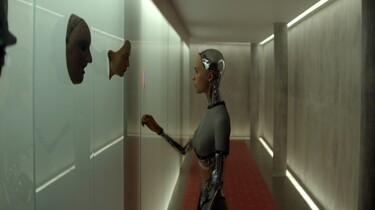 Im Zentrum des Bildes ist Ava zu sehen, sie steht in einem langen Gang und blickt Masken an, die an der Wand angebracht sind.