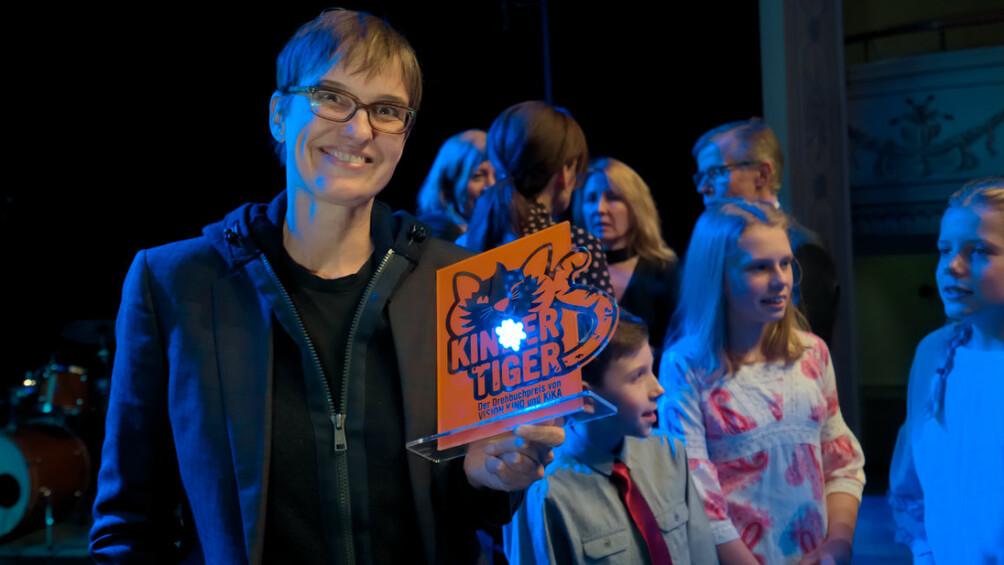 Preisträgerin Natja Brunckhorst mit der Kindertiger-Trophäe, im Hintergrund Mitglieder der Kinderjury