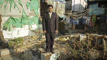 Szenenbild: Ein indischer, gut gekleideter Mann in westlichem Anzug steht auf einer Geröllhalde