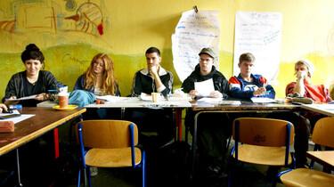 Szenenbild: Blick in Klassenraum, auf die hintere Reihe U-förmig aufgestellter Tische, die Wand ist gelb