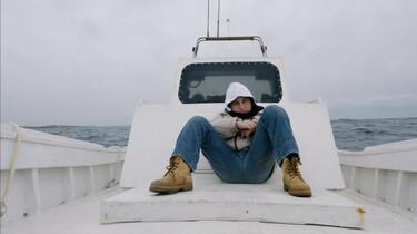 Szenenbild: Samuele liegt im vorderen Teil eines Bootes vor der Brücke