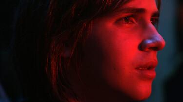 Das in rotes Licht getaucht Gesicht der Hauptfigur im Profill