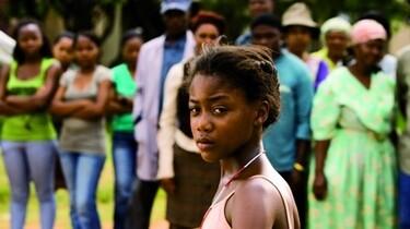 Szenenbild: Ein Mädchen steht vor einer Gruppe von Menschen