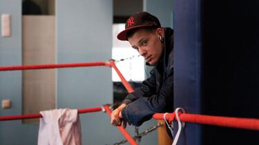 Szenenbild: Ein Junge schaut über ein rotes Geländer