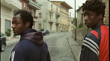 Szenenbild: Zwei Flüchtlinge drehen sich auf einer Straße um