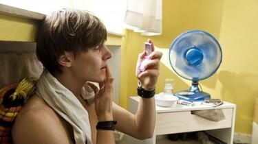 Szenenbild: Lukas sitzt mit nacktem Oberkörper an eine Wand unter einem Fenster gelehnt und betrachtet sich in einem Handspiegel