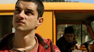 Szenenbild: Der Sohn eines der Mörder vor einem gelben Bus