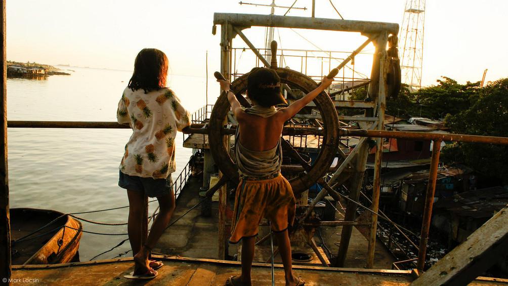 zwei Kinder an einem Steuer auf einem Schiff, gucken in den Horizont.