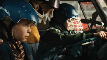 Szenenbild: Ella mit Helm, von der Seite gesehen, in einem Auto