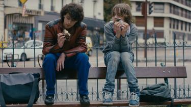 Szenenbild: Mikro und Sprit auf der Lehne einer Bank an einer Straße sitzend, sie essen etwas. Ihre Schulrucksäcke liegen neben ihnen auf der Bank.