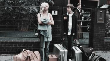 Szenenbild: Der Junge und seine Mutter mit Koffern auf der Straße vor dem Haus