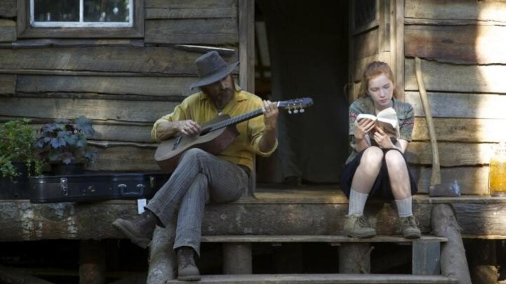 Mann mit Gitarre und Mädchen mit Buch auf der Treppe vor einer Holzhütte
