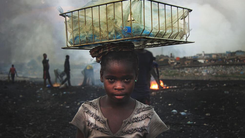 Junges Mädchen mit Korb voller Plastiktüten auf dem Kopf