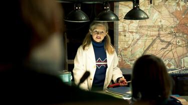 Szenenbild: Die zehnjährige Friederike steht an einem Tisch untd entwickelt einen Plan. Im Hintergrund eine Landkarte