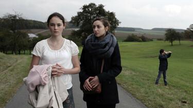Szenenbild: Maria und ein Mädchen gehen auf einem asphaltierten Weg. Im Hintergrund spielt ein Junge auf einer Wiese