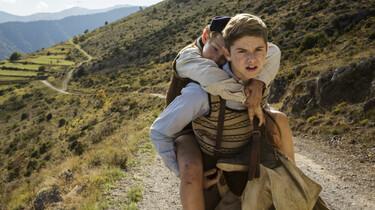 Szenenbild: Auf einer sonnigen, staubigen Straße trägt Maurice seinen jüngeren Bruder Joseph auf dem Rücken