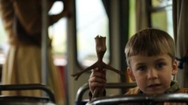 Szenenbild: Der Junge schaut über die Lehne eines Sitzes