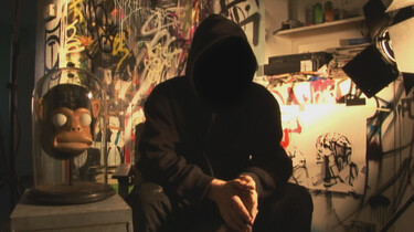 Szenenbild: Mann mit Kapuze auf, so dass sein Gesicht nicht zu sehen ist, vor Graffitti Wand