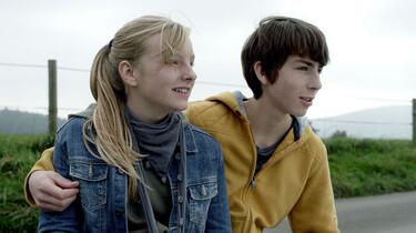 Szenenbild: Johanna und Christian sitzen Arm in Arm auf dem Rand einer Koppel