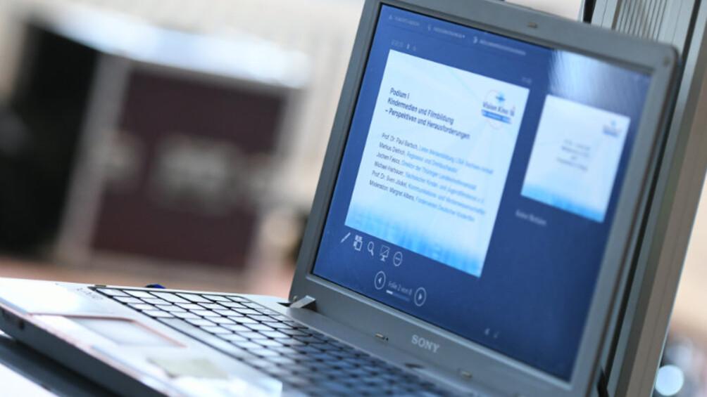 Der bildschirm eines aufgeklappten Laptops mit PPP Präsentation