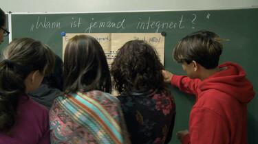 Szenenbild: Schüler und Schülerinnen stehen vor einer Tafel