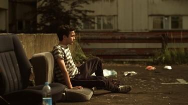Szenenbild: Ali sitzt in einem Hinterhof auf alten Autositzen