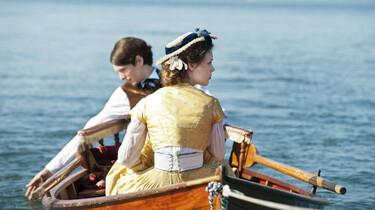 Szenenbild: ein junges Paar in historischen Kostümen in einem Ruderboot auf einem See