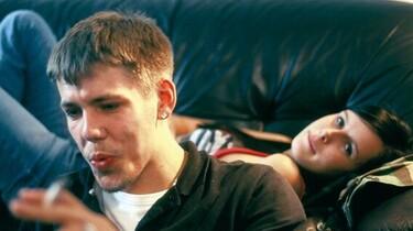 Szenenbild: Im Hintergrund liegt Maggie auf einem Sofa, davor sitzt ein Mann, sein Kopf ist zu sehen