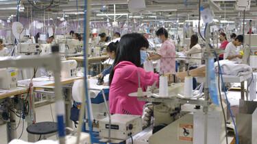 Szenenbild: Näherin mit Mundschutz in einer riesigen Halle mit Nähmaschinen