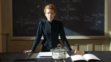 Szenenbild: Marie Curie am Pult, hinter ihr eine Tafel, blickt den Betrachter frontal an