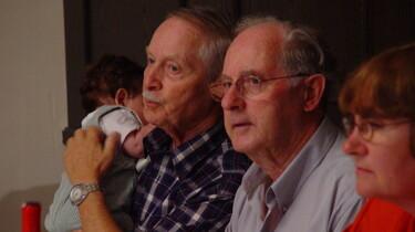 Szenenbild: Zwei alte Männer und eine alte Frau. Einer der Männer hält ein Baby auf dem Arm