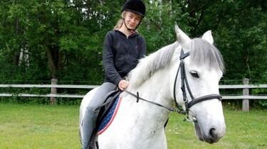 Szenenbild: Klara auf einem weißen Schimmel