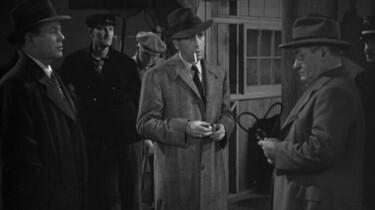 Szenenbild: Eine Gruppe von Männern, unter ihnen Humpfrey Bogart als Philipp Marlow in Trenchcoat und mit Hut