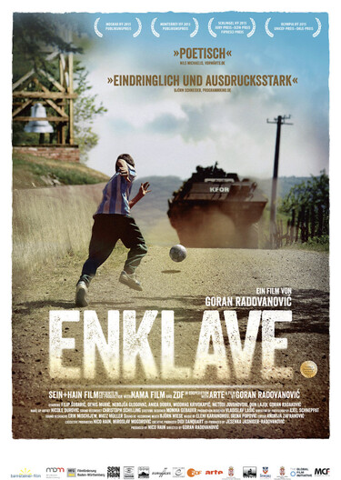 Ein junge rennt einem Ball hinterher, im Hintergrund sieht man einen Panzer.