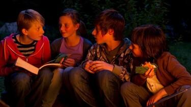 Szenenbild: Eine Kindergruppe im Schein eines Lagerfeuers