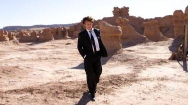 """Szenenbild: Ein Junge steht im Anzug in einer """"Wüste"""""""