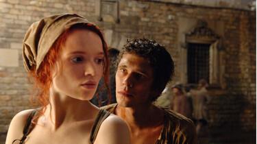 Szenenbild: Leichtbekleidete Frau direkt dahinter ein Mann