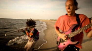 Szenenbild: Luis und Elias, die Straßenmusiker, am Strand