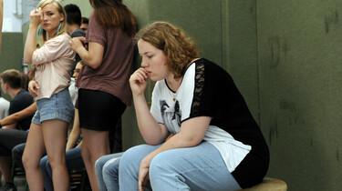 Szenenbild: Cindy alleine auf einer Bank, die anderen Schülerinnen von ihr abgewand