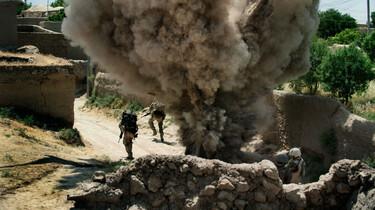 Szenenbild: Zwei Soldaten der Bundeswehr laufen vor einer Explosion davon