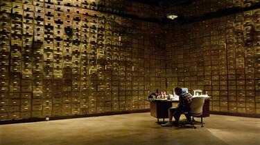 Szenenbild: Gott in seinem Arbeitszimmer, dessen Wände mit Schubladen übersäht sind