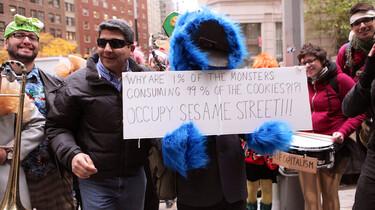 Szenenbild: Gewaltfreier Protest gegen soziale, wirtschaftliche und politische Missstände. Teils verkleidet und gut gelaunt protestieren drei Männer