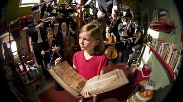 Lili hält ein Buch aufgeschlagen in ihren Händen. Im Hintergrund ist ein Orchester.