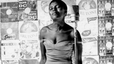 Szenenbild: Miriam Makeba am Mikrofon vor Plakatwand