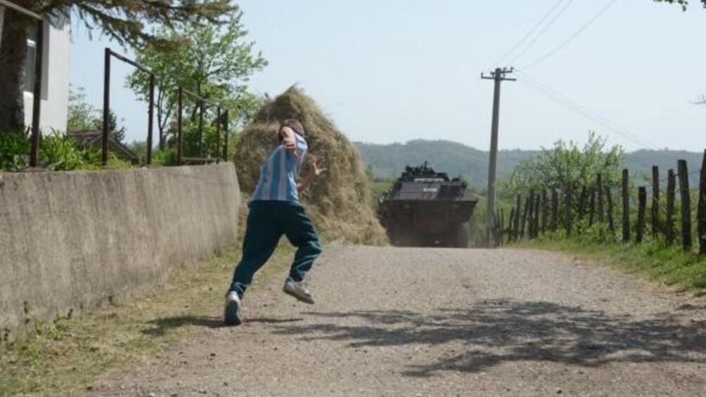 Junge rennt einem Panzer auf einer Landstraße hinterher